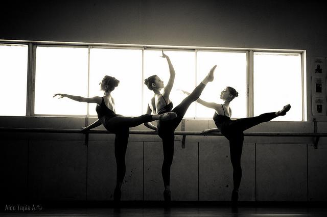 Trois danseuses classiques s'exercent à la barre.