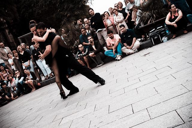 Un homme et une femme dansent le tango dans la rue devant des spectateurs.