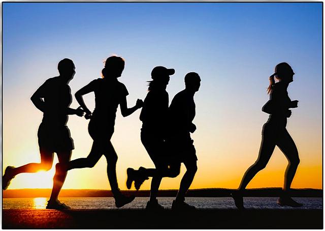 Un groupe de personnes court près de la mer, au coucher du soleil.