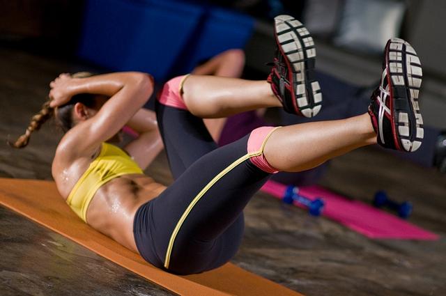 Une femme effectue des exercices sportifs sur un tapis.