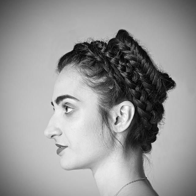 Femme de profil aux cheveux tressés.