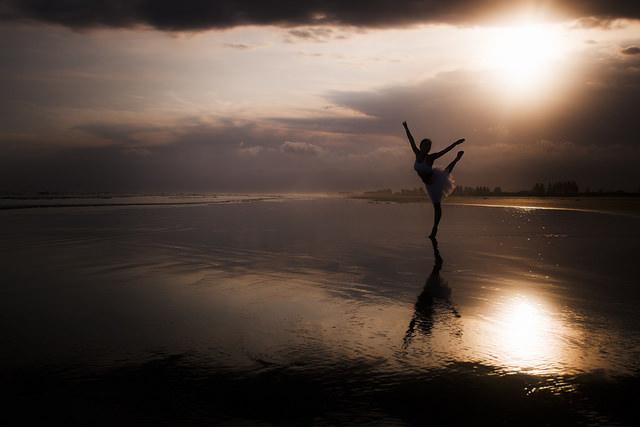 Une danseuse en pleine nature, sur du sable mouillé et lors d'un coucher de soleil.
