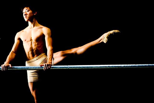 Un danseur s'entraîne contre une barre.