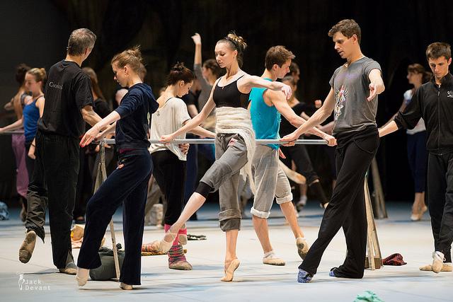 Des danseurs s'échauffent à la barre.