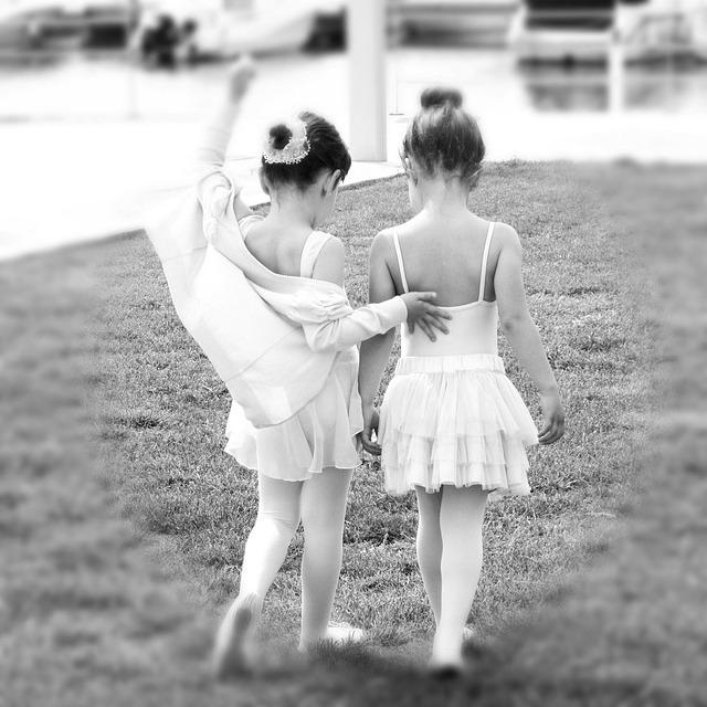 Deux petites filles en tenue de danse, sur une photo en noir et blanc.