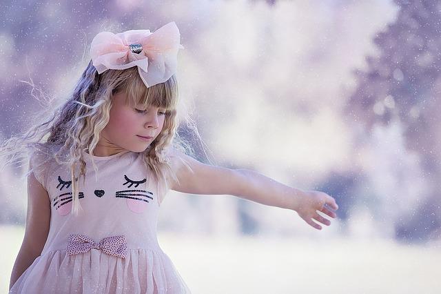 Une petite fille habillée de rose danse.