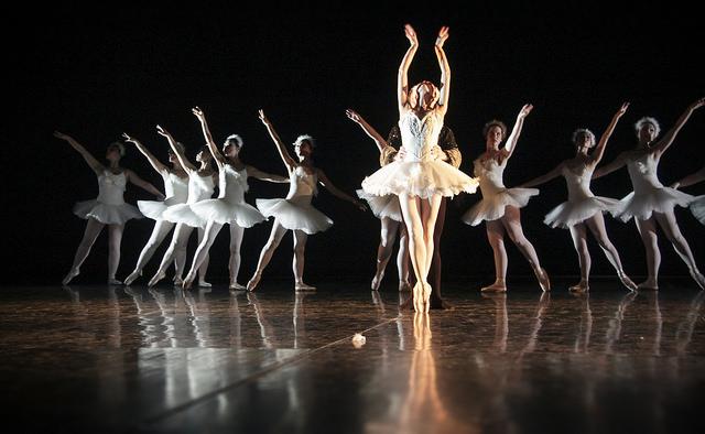 Photographie d'un ballet de Chelsea avec un couple de danseurs émergeant de l'ombre de la scène.