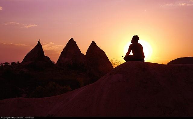 Homme qui médite sur un rocher devant le soleil couchant.
