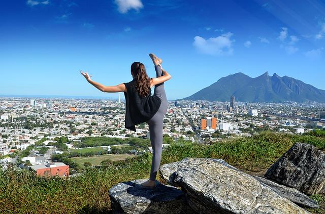 Femme faisant de la danse sur un rocher avec vue sur la ville.