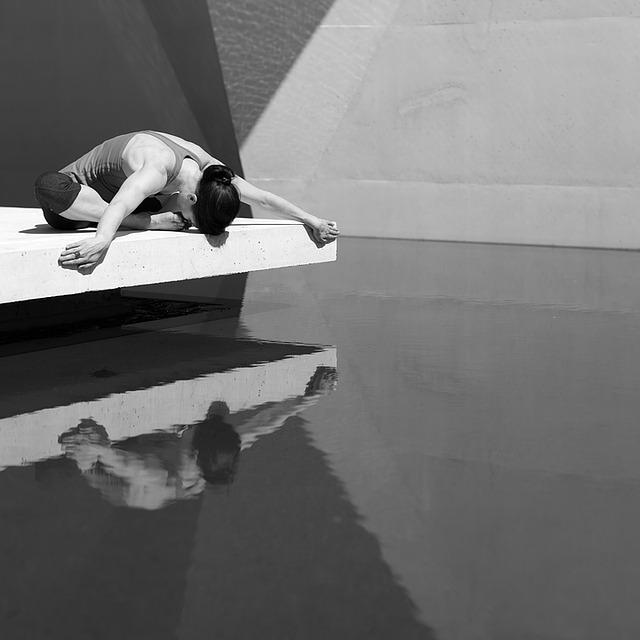 Une femme pratiquant le yoga devant une piscine.