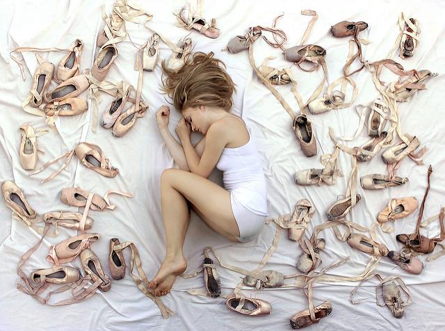 Jeune femme allongée au milieu de chaussons de danse.
