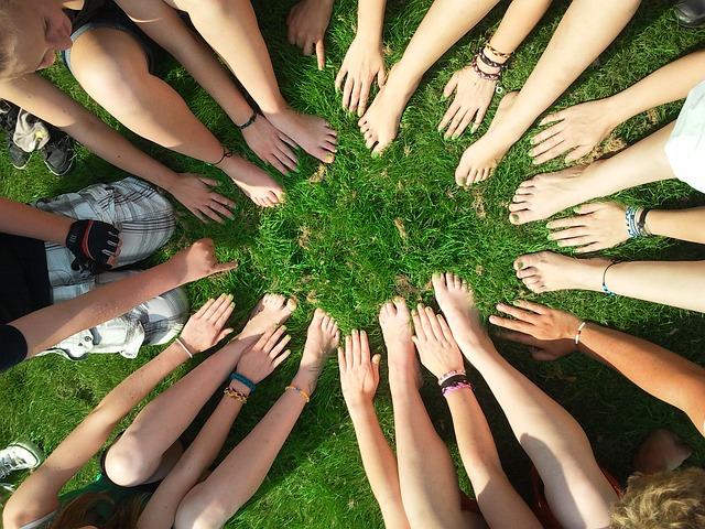 Groupe de jeunes gens formant un cercle avec leurs mains et leurs pieds.