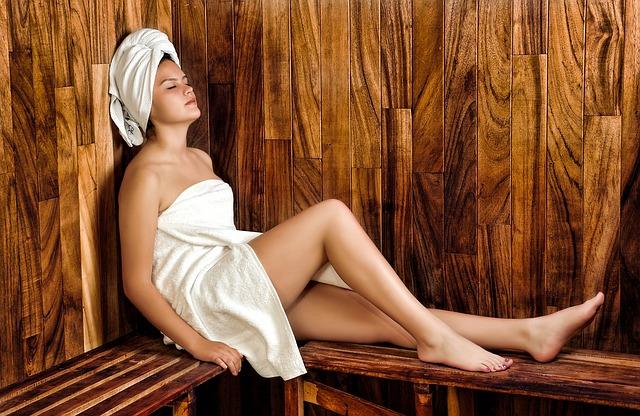 Femme dans un sauna, enroulée dans une serviette éponge blanche.