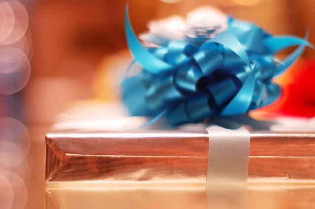 Photographie d'un paquet cadeau dans du papier doré avec un ruban bleu.