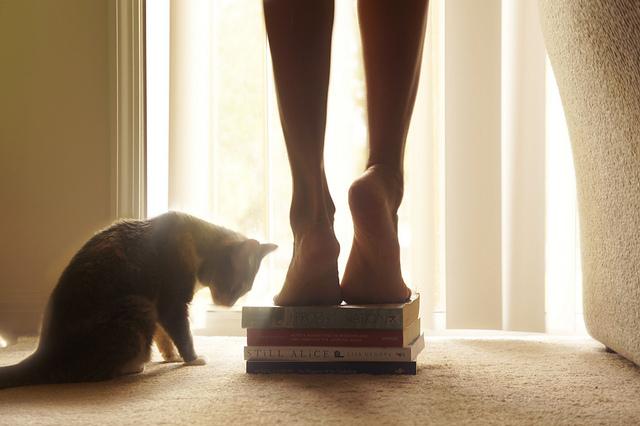 Pieds de femme sur une pile de bouquins, avec un chat à côté.