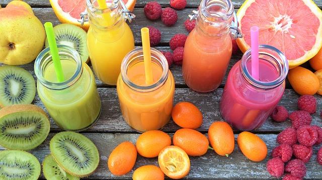 Smoothies colorés et vitaminés, entourés de fruits frais coupés.