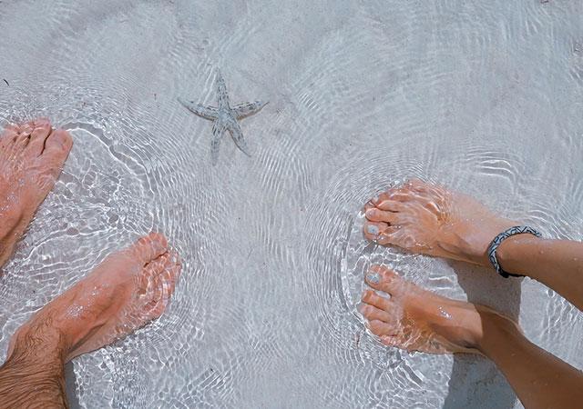 Photographie de pieds dans l'eau de la mer..