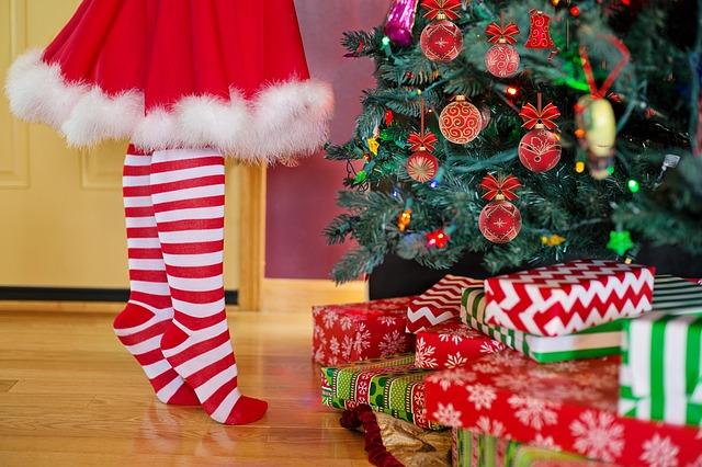 Une enfant cherche ses cadeaux sous le sapin au matin de Noël.