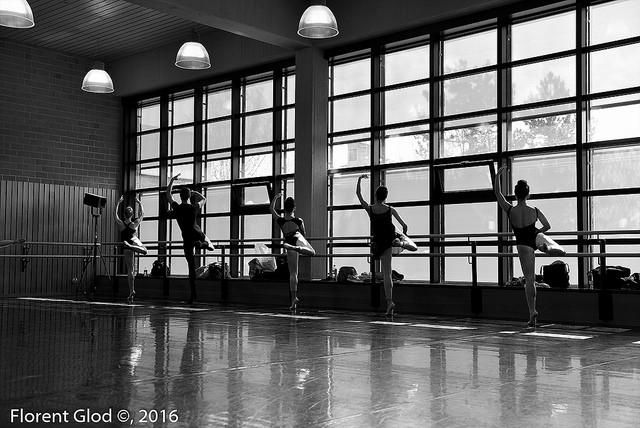 Danseurs et danseuses classiques qui s'échauffent à la barre.