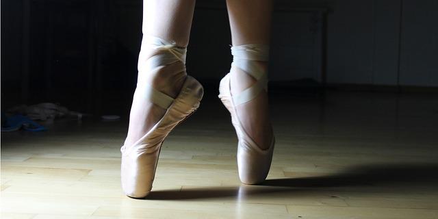 Pieds d'une danseuse en train de faire des pointes en chaussons de danse.