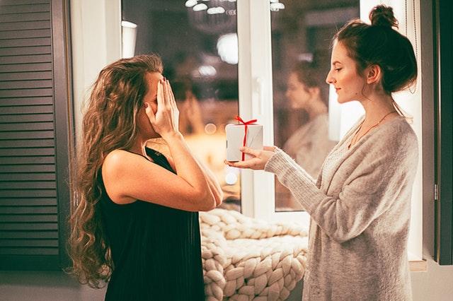 Jeune femme offrant un cadeau de danse à une amie qui se cache les yeux.