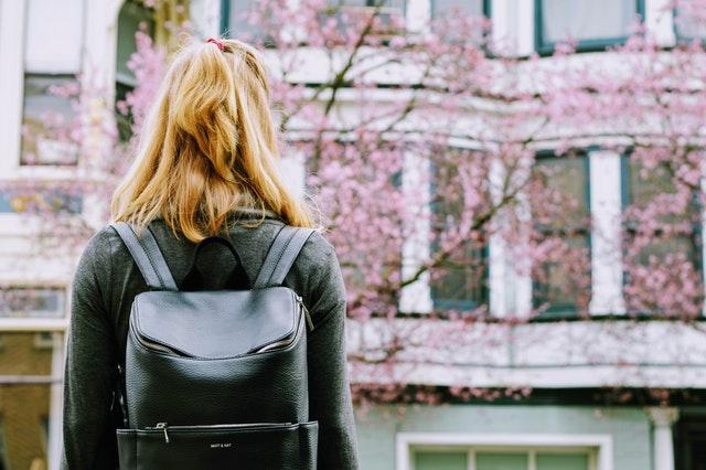 Fille de dos portant un sac à dos noir.
