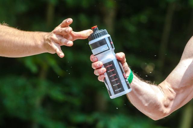 Deux hommes se passent une boisson pendant une session de sport.