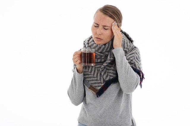 Personne qui boit une tisane pour soigner un rhume.