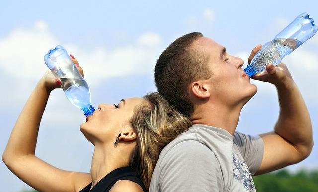 Une femme et un homme, dos à dos, boivent de l'eau.