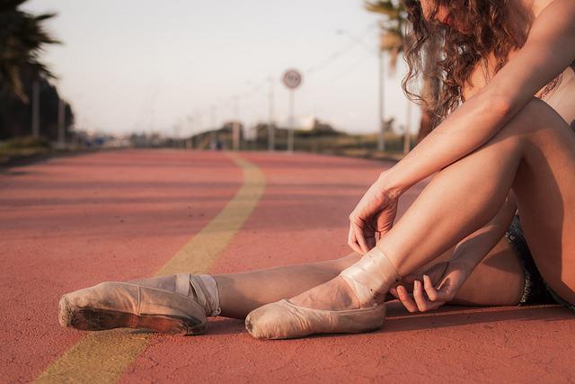 Danseuse en pointes de danse sur une piste d'athlétisme.