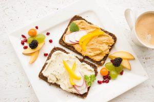 Petit déjeuner composé de tartines de pain complet avec hoummous et fromage, ainsi que quelques fruits.