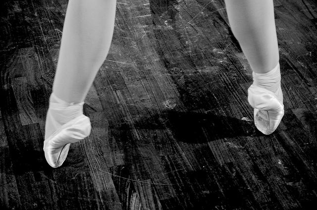 Photographie en noir et blanc d'un danseur en train de s'exercer.