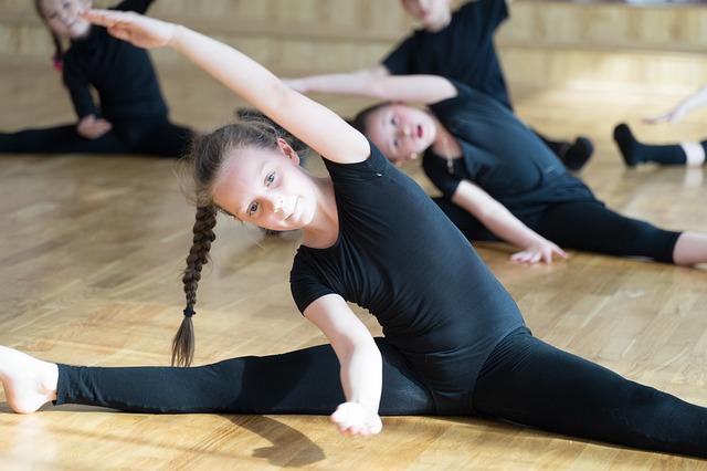Groupe de petites filles en tenue de danse classique pendant un échauffement.