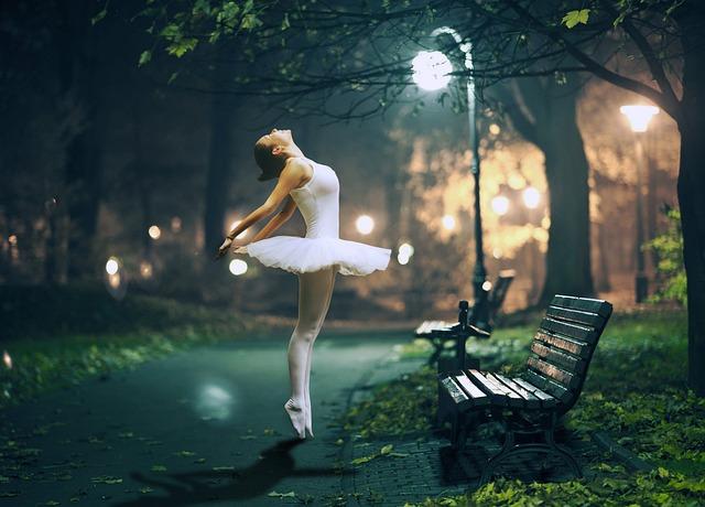 Femme en tenue de danse classique dans la rue, de nuit.