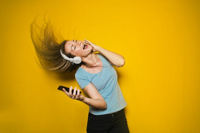 Jeune femme en train de danser, heureuse de profiter des soldes en ligne.