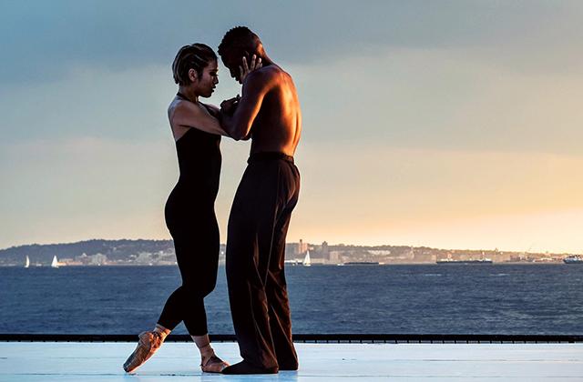 Danseurs en justaucorps noir devant la mer.