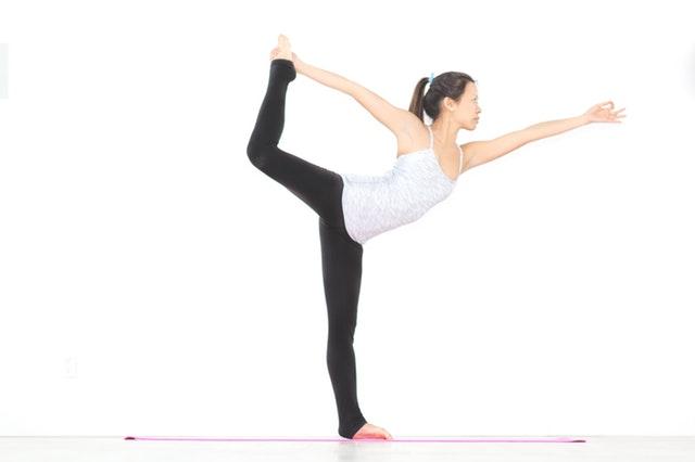 Jeune femme en train de s'échauffer avant son cours de danse.