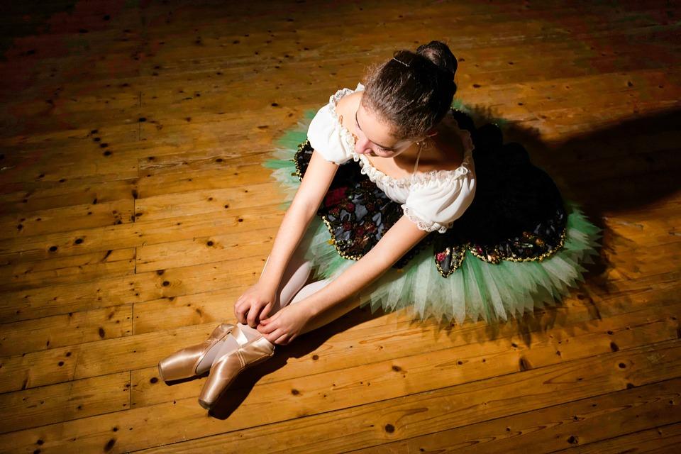 Danseuse assise sur le parquet.