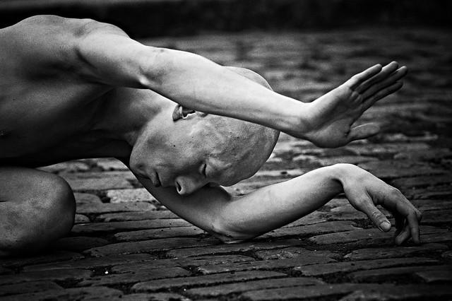 Un homme allongé qui regarde vers le sol.