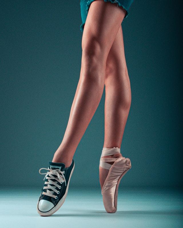 Danseuse qui porte une pointe à un pied et une tennis à l'autre.