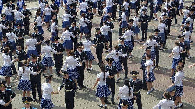 Personnes dansant la valse en uniforme sur une place